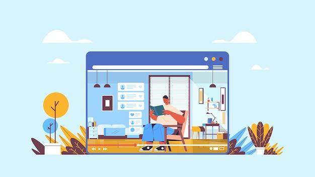 Mężczyzna bloger czytanie książki nagrywanie online blog wideo transmisja strumieniowa na żywo koncepcja blogowania mężczyzna vlogger w oknie przeglądarki internetowej wnętrze salonu w poziomie