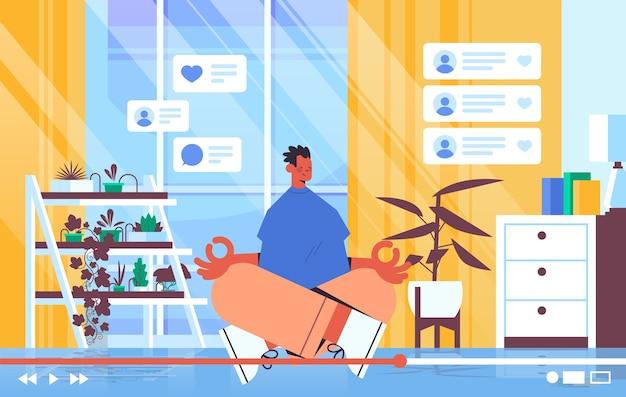 Mężczyzna bloger fitness nagrywanie online blog wideo transmisja strumieniowa na żywo blogowanie vlog popularność koncepcja mężczyzna vlogger siedzi pozycja lotosu salon wnętrze poziomo