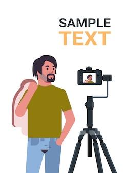 Mężczyzna blogger nagrywanie wideo blog z aparatem cyfrowym na statywie transmisja na żywo media społecznościowe blogowanie koncepcja portret pionowe miejsce