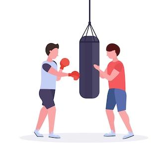 Mężczyzna bokser z osobistym trenerem uderza worek treningowy w czerwone rękawice bokserskie facet wojownik trening trening koncepcja zdrowego stylu życia biały