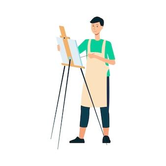 Mężczyzna brunet malarz i artysta w fartuchu rysuje pędzlem po sztalugach.