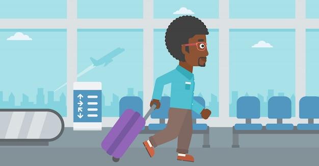 Mężczyzna chodzi z walizką na lotnisku.