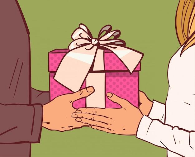Mężczyzna daje teraźniejszości lub prezenta pudełku kobieta wręcza zbliżenie
