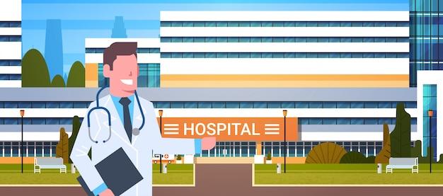 Mężczyzna doktor stałego nad szpitalnym budynkiem zewnętrznego punktu ręka na nowoczesnej klinice