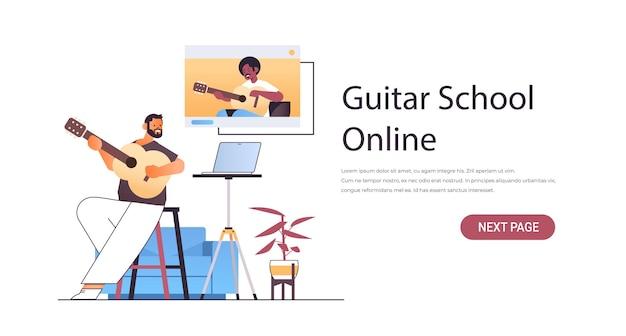 Mężczyzna gra na gitarze z afrykańskim nauczycielem w oknie przeglądarki internetowej podczas wirtualnej konferencji