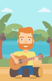 Mężczyzna gra na gitarze.