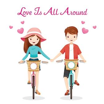 Mężczyzna i kobieta jeżdżą na rowerze, zaciskając ręce, miłość jest wszędzie