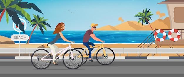 Mężczyzna i kobieta na rowerze w tropikalnej, piaszczystej plaży.