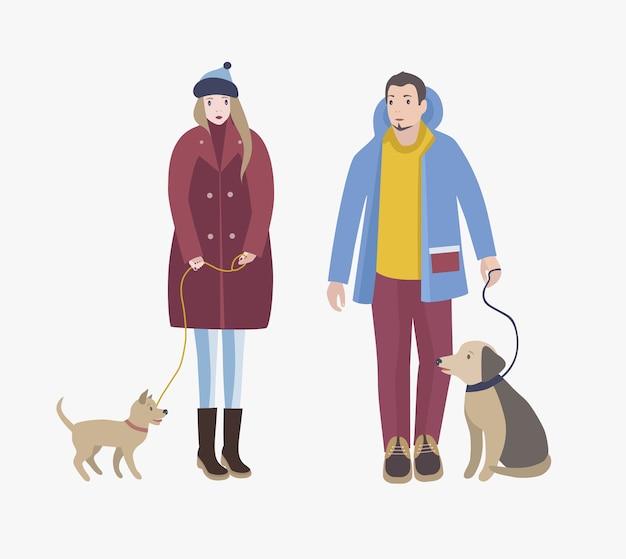 Mężczyzna i kobieta ubrani w zimowe ubrania stoją, trzymają psy na smyczy i patrzą na siebie. postaci z kreskówek ze zwierzętami na białym tle. kolorowa ilustracja wektorowa.