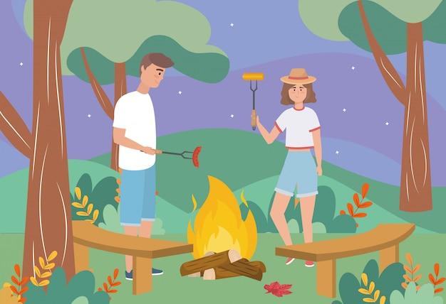 Mężczyzna i kobieta w drewnianym ogniu z kiełbasą i kolbami