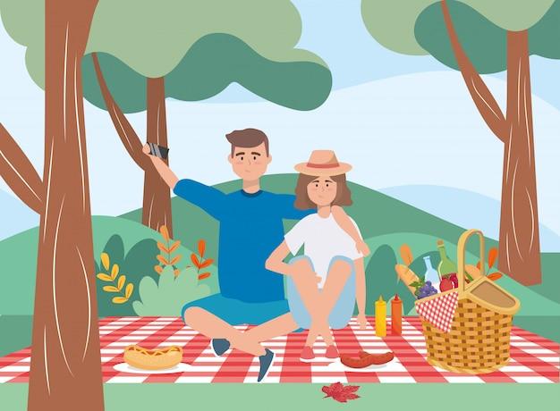 Mężczyzna i kobieta w obrusie z koszem i jedzeniem