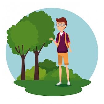 Mężczyzna jest ubranym szkła z backapck i drzewa z krzakami