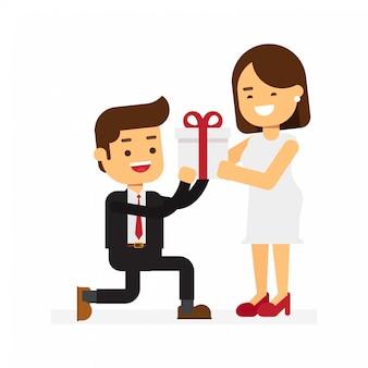 Mężczyzna klęka i dać pudełko dla ładnej kobiety