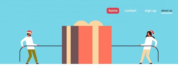 Mężczyzna kobieta ciągnie przeciwne końce linowe pudełko prezentowe na świąteczną stronę docelową