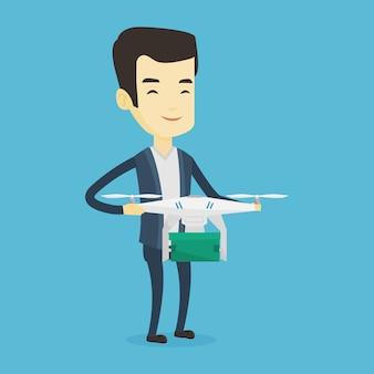Mężczyzna kontrolujący drona dostarczającego z paczką pocztową