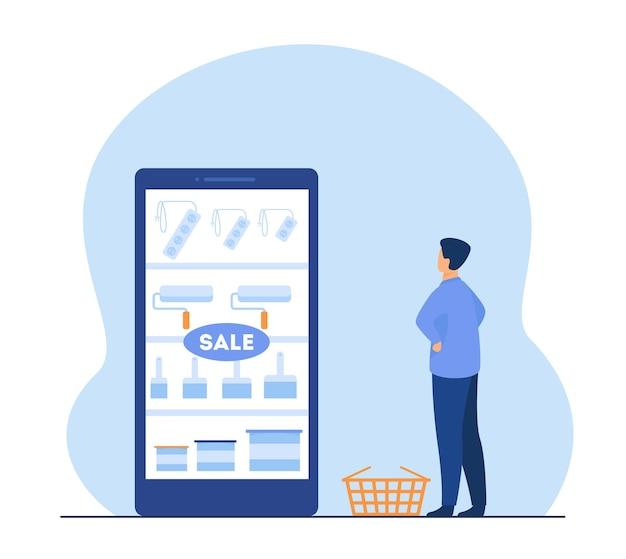 Mężczyzna kupujący online narzędzia do malowania. zakupy internetowe, wałki, pędzle. ilustracja kreskówka