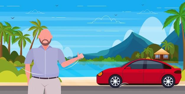 Mężczyzna łapanie auto udostępnianie samochodu usługi transportowe koncepcja lato wakacje tropikalny wyspa pejzaż morski tło poziome portret