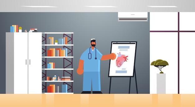 Mężczyzna lekarz kardiolog w mundurze przedstawiając tablicę typu flip chart z ludzkim sercem medycyna koncepcja opieki zdrowotnej nowoczesny szpital klinika medyczna biuro wnętrze pełnej długości płaskie poziome