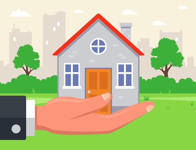 Mężczyzna ma dom na ręku na tle miasta. sprzedaż nieruchomości podmiejskich. ilustracja.