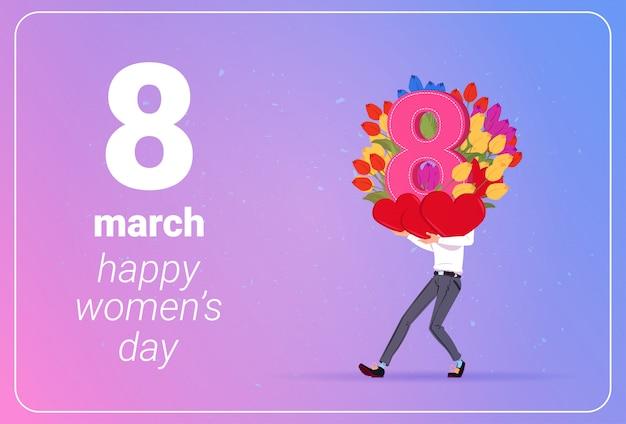 Mężczyzna mienia tulipanów kwiaty i czerwoni serca szczęśliwy kobieta dnia 8 marcowy wakacyjny pojęcie