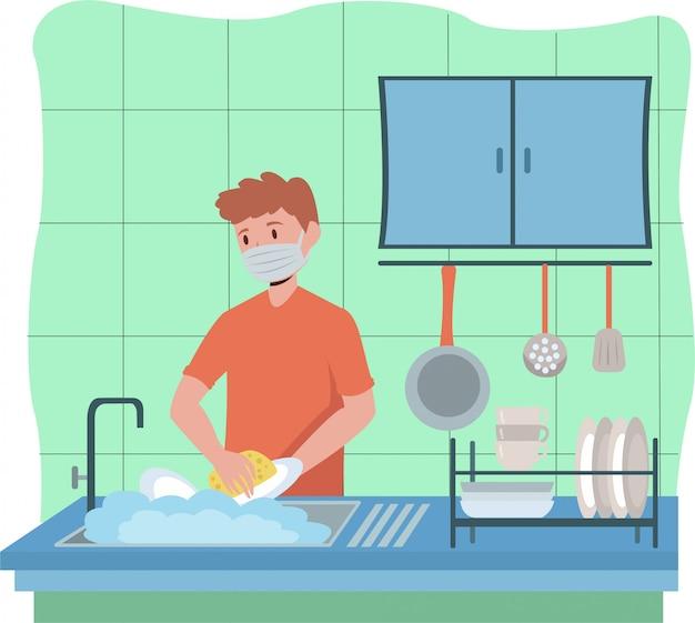 Mężczyzna myje naczynia, wciąż używając maski medycznej
