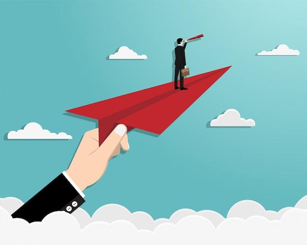 Mężczyzna na papierowym samolocie w niebie
