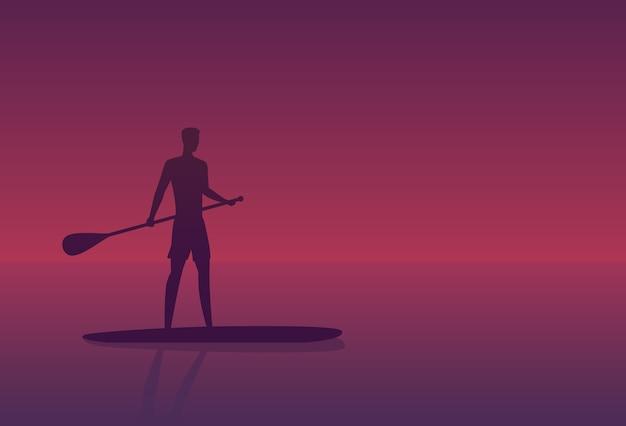 Mężczyzna na pokładzie sup o zachodzie słońca