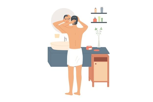 Mężczyzna nakłada produkt do pielęgnacji włosów przed lustrem.