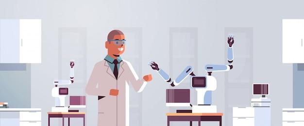 Mężczyzna naukowiec w pobliżu ramię robota przemysłowego