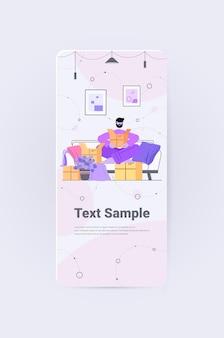 Mężczyzna otwierający kartonowe pudło rozpakowywanie dostarczanie poczty zamawianie online przez internet koncepcja pionowa kopia na całej długości