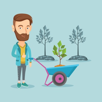 Mężczyzna pcha taczki z rośliną.