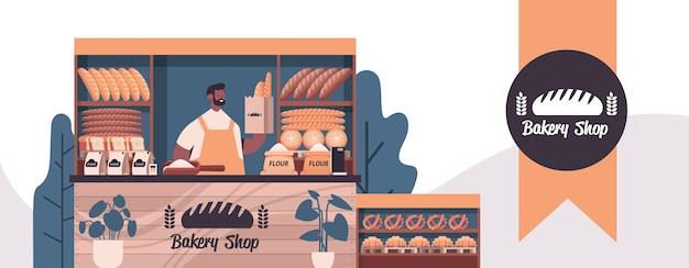 Mężczyzna piekarz trzymając torbę z bagietkami mężczyzna w mundurze sprzedaży świeżych produktów piekarniczych w piekarni portret poziomej ilustracji wektorowych
