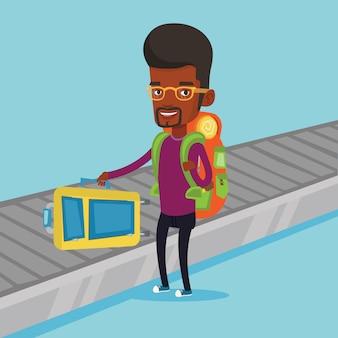 Mężczyzna podnosi walizkę na przenośnika bagażu