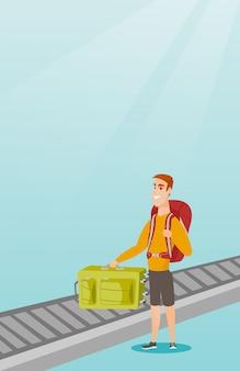 Mężczyzna podnosi walizkę z przenośnika taśmowego.