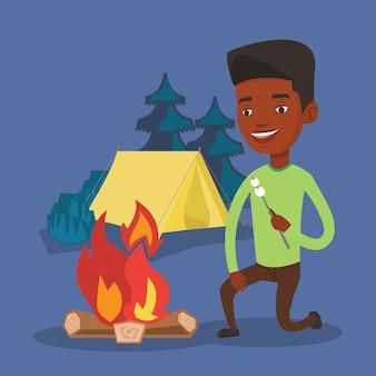 Mężczyzna prażenie zefir nad ogniskiem.