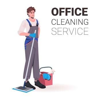 Mężczyzna profesjonalny sprzątacz biurowy woźny w mundurze z miejscem do czyszczenia sprzętu do czyszczenia
