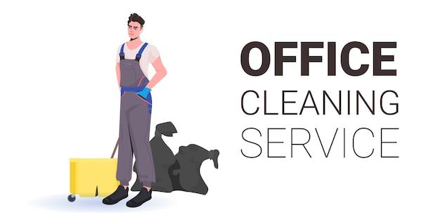 Mężczyzna profesjonalny sprzątacz biurowy woźny w mundurze ze sprzętem do czyszczenia kopia przestrzeń pozioma