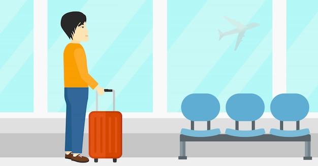 Mężczyzna przy lotniskiem z walizką