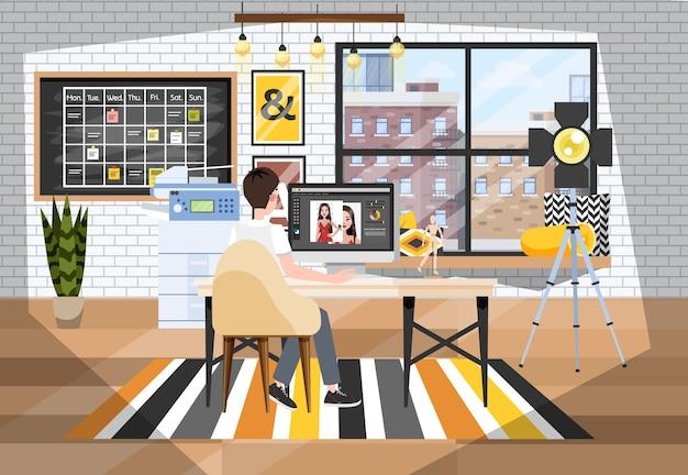 Mężczyzna retuszuje zdjęcie na komputerze. budynek photostudio
