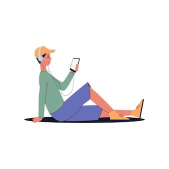 Mężczyzna siedzący na podłodze ze słuchawkami słuchający muzyki i patrząc na ekran swojego telefonu z uśmiechem - słuchacz audio ze smartfonem,