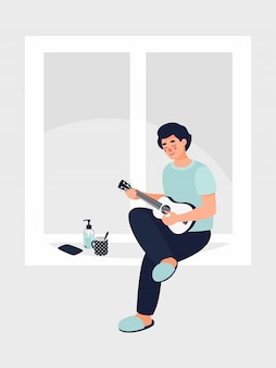 Mężczyzna siedzi i gra na gitarze w oknie w domu.