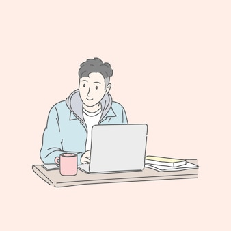 Mężczyzna siedzi i za pomocą laptopa