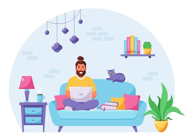 Mężczyzna siedzi na kanapie i pracuje na laptopie domowe biuro freelancer