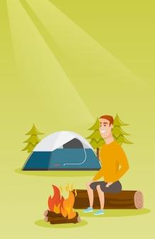 Mężczyzna siedzi na kłodzie w pobliżu ogniska na kempingu.