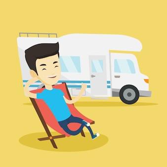 Mężczyzna siedzi na krześle przed samochód kempingowy.