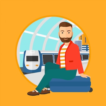 Mężczyzna siedzi na walizce na dworcu.