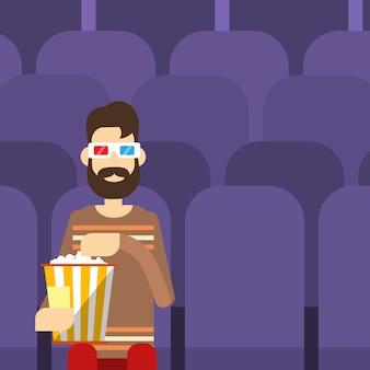 Mężczyzna siedzi oglądając film w kinie 3d okulary z popcornem