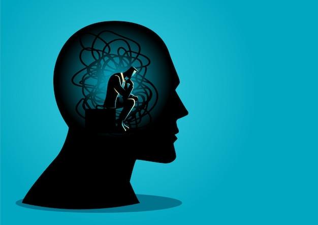 Mężczyzna siedzi w ludzkiej głowie z splątanymi sznurkami