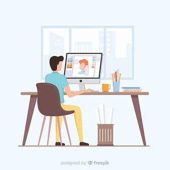 Mężczyzna siedzi w miejscu pracy projektanta graficznego