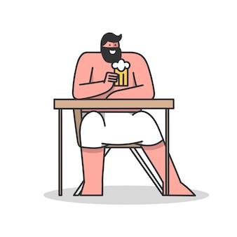 Mężczyzna siedzi w saunie przy stole owinięty ręcznikiem i kubkiem do picia